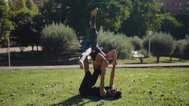 Schönes-paar-praktizieren-Acro-Yoga-am-Morgen