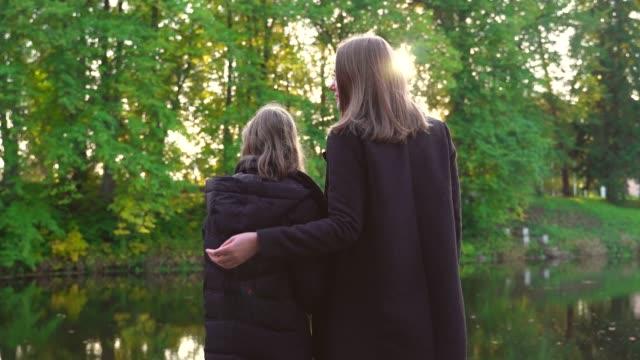 Frau-und-ihre-Tochter-stehen-in-der-Nähe-des-Teiches-