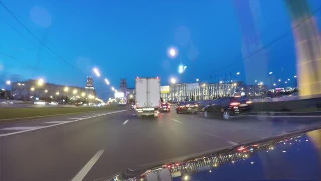 Conducir-en-una-ciudad-de-noche-calle-Lapso-de-tiempo-de-Movimiento-borroso-Vista-desde-fuera-de-la-cabina-