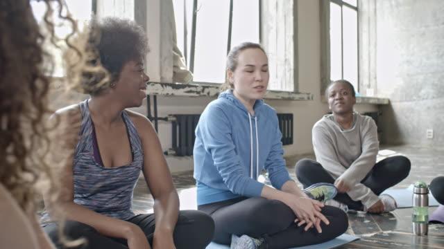 Fröhliche-Frauen-im-Chat-vor-der-Yogastunde