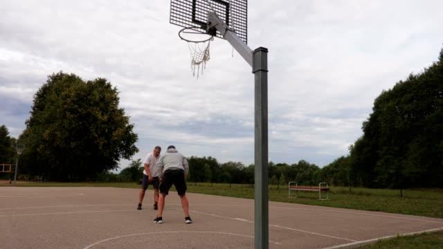 Zwei-Männer-spielen-Basketball-im-freien
