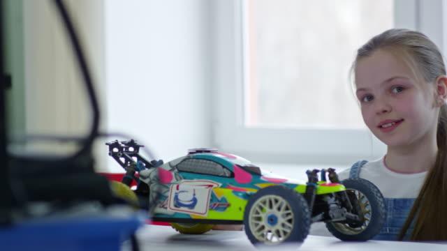 Chica-jugando-con-el-coche-de-juguete-y-sonriendo