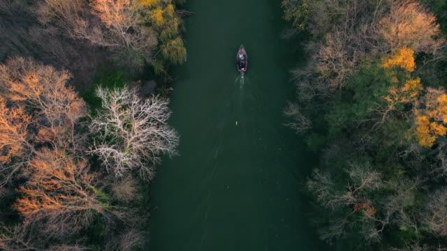 Fluss-und-die-Herbst-Bäume-und-Segeln-Angelboot/Fischerboot-bei-Sonnenuntergang-Luftbild-Drohne-video