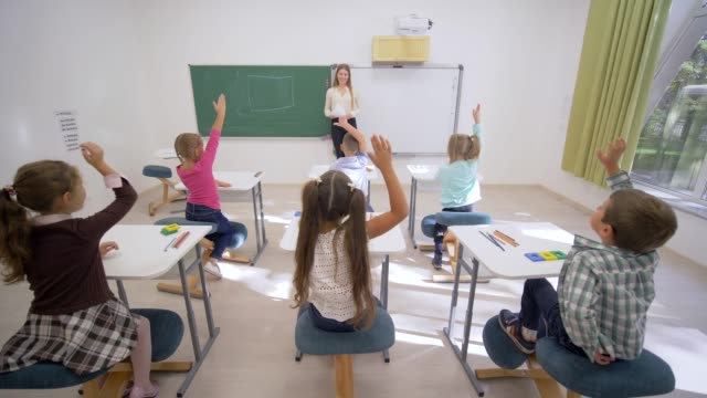 group-of-schoolkids-raise-hands-to-answer-at-lesson-while-sitting-at-desk-in-front-of-teacher-to-board-in-elementary-school