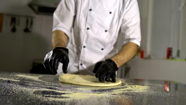 Cook-in-the-kitchen-preparing-pizza-dough-A-man-prepares-pastries