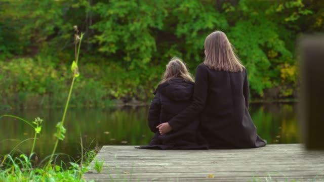Frau-und-ihre-Tochter-sitzen-in-der-Nähe-des-Teiches-