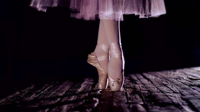 Nahaufnahme,-Strahlen-der-Scheinwerfer,-auf-der-Bühne-des-alten-Theaters-Halle.-Ballerina-in-weißen-Rock,-wirft-auf-Zehen-in-Pointe,-führt-elegant-eine-gewisse-Übung-Ballett,-Pas-de-Bourre-suivi