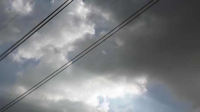 Gray-bedeckt-Wolken-am-blauen-Himmel-vor-Regen-oder-Sturm-Stromleitungen-gehen-durch-den-Himmel-