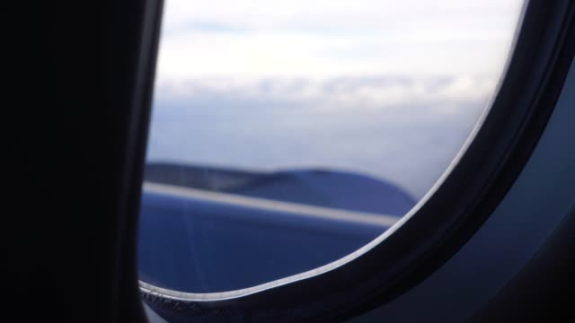 Airplane-window-view-of-clouds-from-passenger-seat