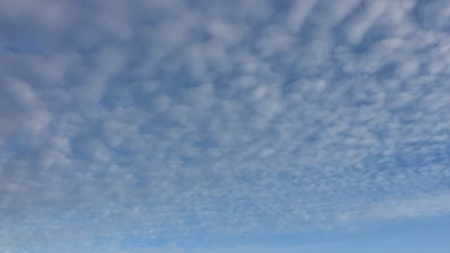 Cloudy-sky-White-clouds-disappear-in-the-hot-sun-on-blue-sky-Time-lapse-motion-clouds-blue-sky-background-Blue-sky-with-white-clouds-and-sun-