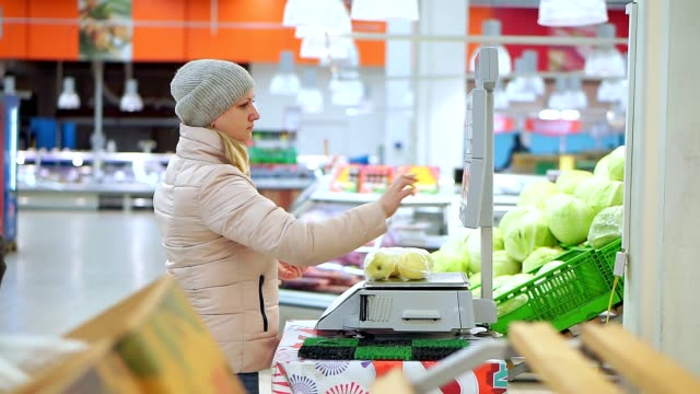 Woman-in-winter-clothes-in-the-supermarket-weighing-apples-on-scales-She-chooses-the-code-and-value-of-the-fruit-