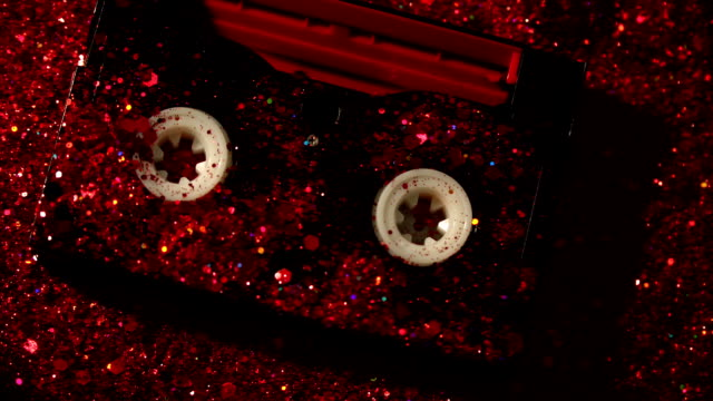 Black-video-cassette-on-the-background-of-red-glitter
