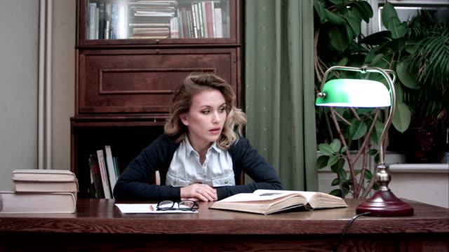 Frustrated-woman-impatiently-looking-at-papers-and-books-on-her-desk-slamming-her-fists-on-the-table