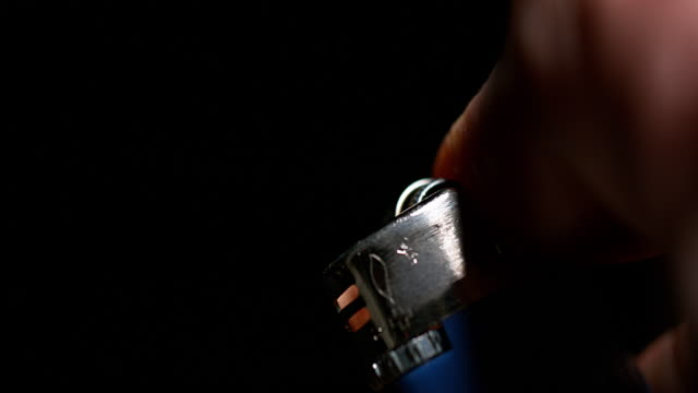 Hand-of-Man-who-Lights-a-Lighter-on-Black-Background-Slow-Motion-4K