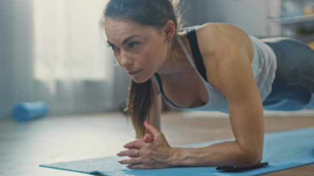 Strong-Beautiful-Fitness-Girl-in-Athletic-Workout-Clothes-is-Making-a-Plank-Exercise-While-Using-a-Stopwatch-on-Her-Phone-She-is-Training-at-Home-in-Her-Living-Room-with-Cozy-Interior-
