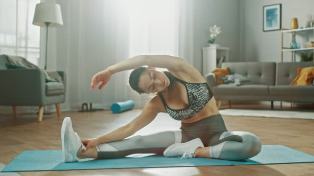 Beautiful-Busty-Fitness-Girl-in-an-Athletic-Top-is-Doing-Stretching-Yoga-Exercises-in-Her-Bright-and-Spacious-Living-Room-with-Modern-Interior-