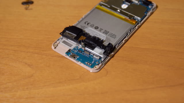 Repair-a-cell-phone-on-a-brown-table-Close-up-of-the-hands-of-a-man