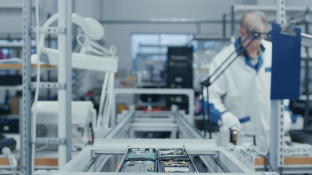 Time-Lapse-of-Electronics-Factory-Workers-Assembling-Smartphone-Circuit-Boards-by-Hand-While-they-Move-on-the-Assembly-Line-High-Tech-Factory-Facility-