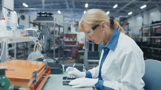 Senior-Electronics-Factory-Workers-in-White-Work-Coats-Inserting-Microchips-Processors-and-Semiconductors-into-Printed-Circuit-Boards-for-Smartphones-High-Tech-Factory-Facility-Footage-with-Time-Lapse-Frames-