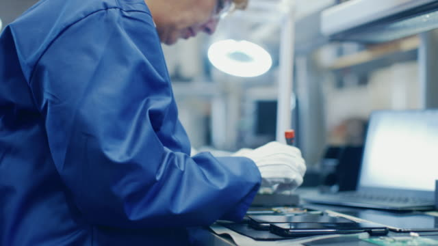 Woman-Electronics-Factory-Worker-in-Blue-Work-Coat-and-Protective-Glasses-is-Assembling-Smartphones-with-Screwdriver-High-Tech-Factory-Facility-with-more-Employees-in-the-Background-