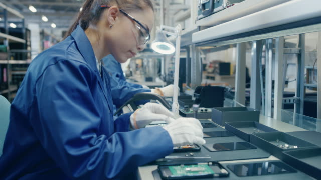 Female-Electronics-Factory-Worker-in-Blue-Work-Coat-and-Protective-Glasses-is-Assembling-Smartphones-with-Screwdriver-High-Tech-Factory-Facility-with-more-Employees-in-the-Background-
