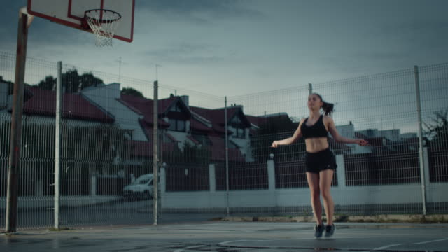 Beautiful-Energetic-Fitness-Girl-Skipping/Jumping-Rope-She-is-Doing-a-Workout-in-a-Fenced-Outdoor-Basketball-Court-Evening-Footage-After-Rain-in-a-Residential-Neighborhood-Area-