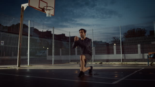 Strong-Muscular-Fit-Young-Man-in-Sport-Outfit-Doing-Forward-Lunge-Exercises-He-is-Doing-a-Workout-in-a-Fenced-Outdoor-Basketball-Court-Evening-Footage-After-Rain-in-a-Residential-Neighborhood-Area-