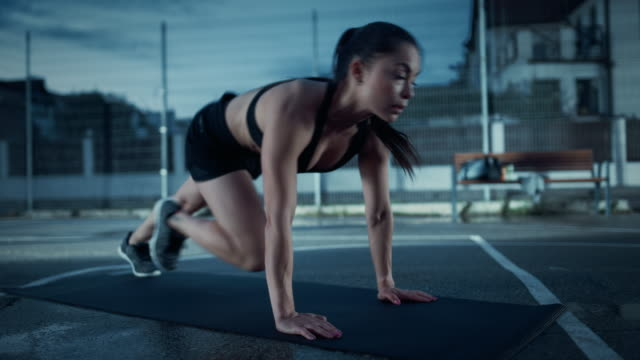 Beautiful-Energetic-Fitness-Girl-Doing-Mountain-Climber-Exercises-She-is-Doing-a-Workout-in-a-Fenced-Outdoor-Basketball-Court-Evening-Footage-After-Rain-in-a-Residential-Neighborhood-Area-