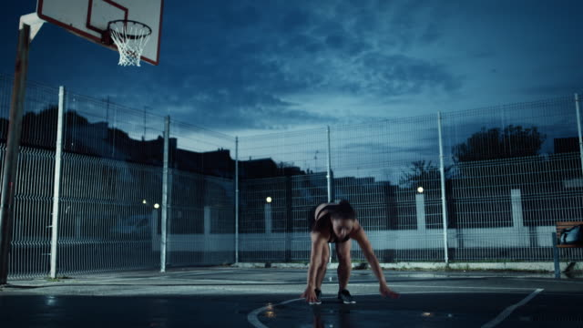 Adecuación-energética-hermosa-chica-haciendo-ejercicios-Jack-Burpee-Ella-está-haciendo-un-entrenamiento-en-una-cancha-de-baloncesto-al-aire-libre-cercado-Imágenes-de-noche-después-de-la-lluvia-en-una-zona-de-barrio-residencial-