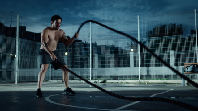 Strong-Muscular-Fit-Shirtless-Young-Man-is-Doing-Exercises-with-Battle-Ropes-He-is-Doing-a-Workout-in-a-Fenced-Outdoor-Basketball-Court-Evening-Footage-After-Rain-in-a-Residential-Neighborhood-Area-