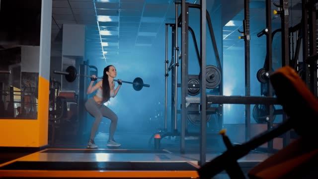 Chica-se-pone-en-cuclillas-con-una-barra-Humo-oscuridad-gimnasio