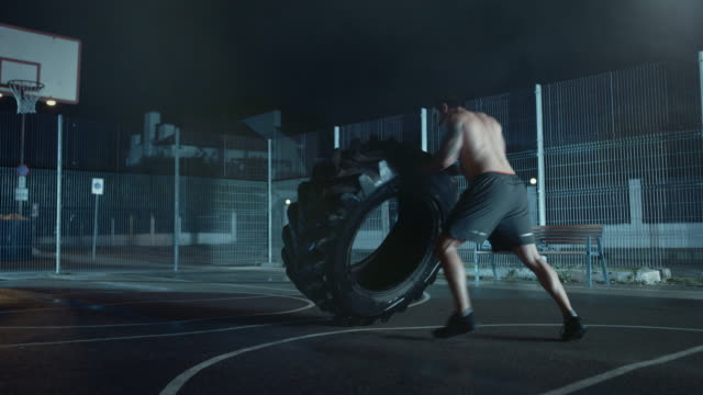 Strong-Muscular-Fit-Young-Shirtless-Man-is-Doing-Exercises-in-a-Fenced-Outdoor-Basketball-Court-He-s-Flipping-a-Big-Heavy-Tire-in-a-Foggy-Night-After-Rain-in-a-Residential-Neighborhood-Area-