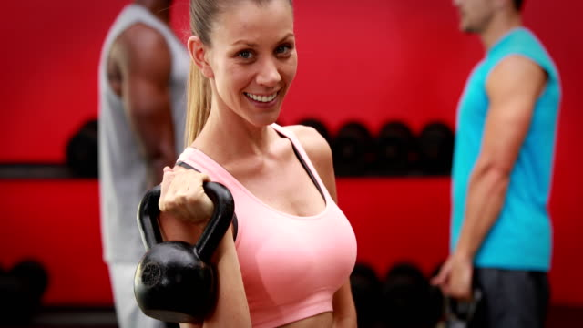 Woman-holding-kettlebell-in-gym-gym