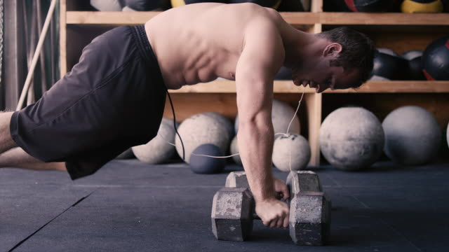 A-fit-young-man-doing-push-ups-with-dumbbells-in-a-gym