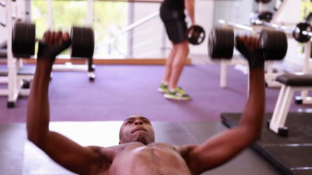 Fit-shirtless-man-lifting-dumbbells-lying-on-bench