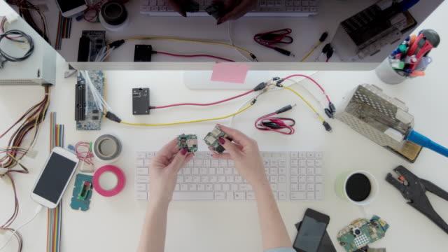 Female-electronics-engineer-examining-circuit-board