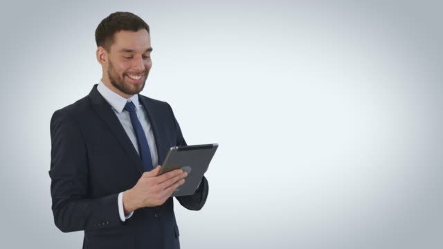 Mid-Shot-of-a-Smiling-Businessman-Using-Tablet-Computer-Shot-on-a-White-Background-