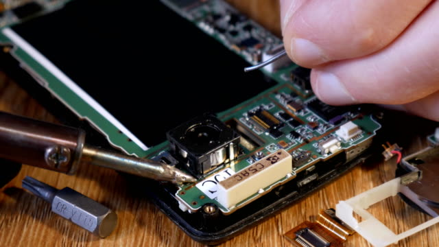 Soldering-smartphone-to-connect-two-contacts