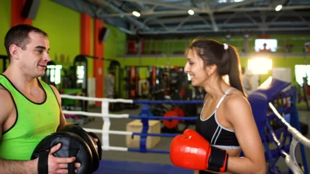 La-joven-boxeador-habla-con-el-entrenador-del-hombre-sonriendo-en-el-Club-de-boxeo
