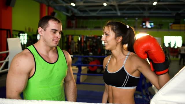 Mujer-joven-boxerand-su-entrenador-sonriendo-y-divertirse-en-el-ring-de-boxeo