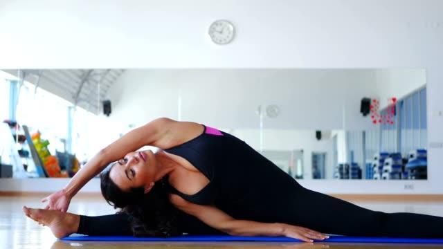 Bonita-mujer-entrenamiento-flexibilidad-en-el-gimnasio-en-MAT