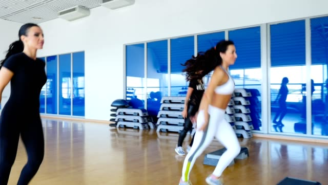 Young-sporty-women-training-the-step-aerobics-in-the-gym