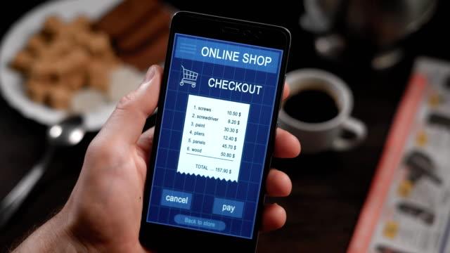 Pagar-una-receta-store-con-una-aplicación-de-smartphone-En-el-marco-de-las-manos-del-hombre-una-persona-paga-para-las-compras-en-una-tienda-en-línea-vía-Internet-y-su-smartphone-Para-materiales-de-construcción-y-herramientas