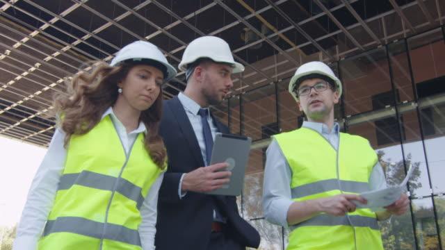 Equipo-de-dos-ingenieros-y-empresario-en-Hard-Hat-caminando-hablando-y-usando-Tablet-Computer-Edificio-de-cristal-o-rascacielos-en-construcción-en-segundo-plano-
