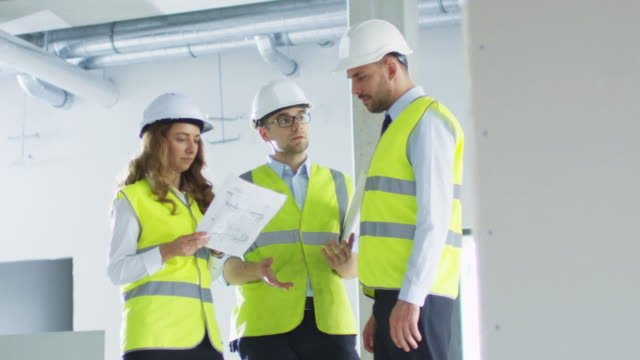 Equipo-de-ingenieros-en-sombreros-duros-teniendo-conversación-mirando-Blueprint-dentro-del-edificio-en-construcción-