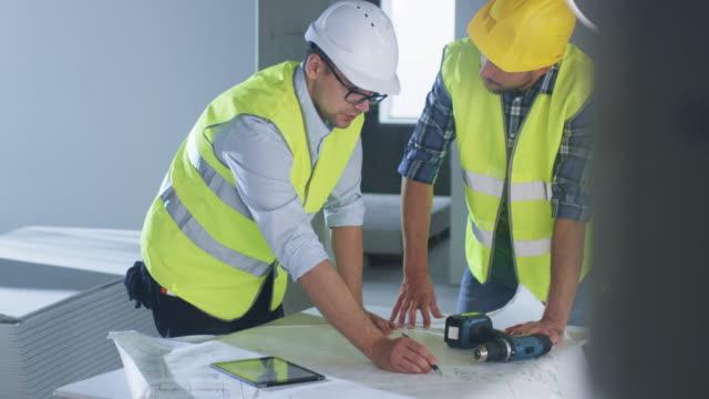 Equipo-de-ingenieros-son-flexión-plano-grande-y-tener-conversación-dentro-de-edificio-en-construcción-