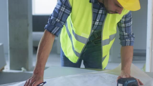 Trabajador-de-la-construcción-en-casco-agacharse-y-mirar-en-general-proyecto-en-edificio-en-construcción-