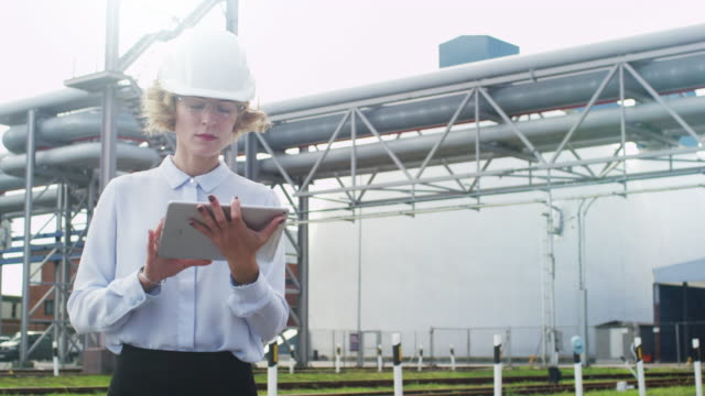 Woman-in-Hard-Hat-is-Walking-and-Using-Tablet-PC-in-Industrial-Environment