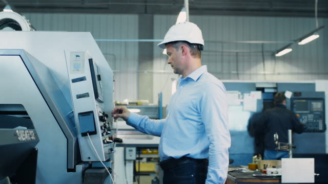 El-ingeniero-está-configurando-la-máquina-de-torno-CNC-en-fábrica