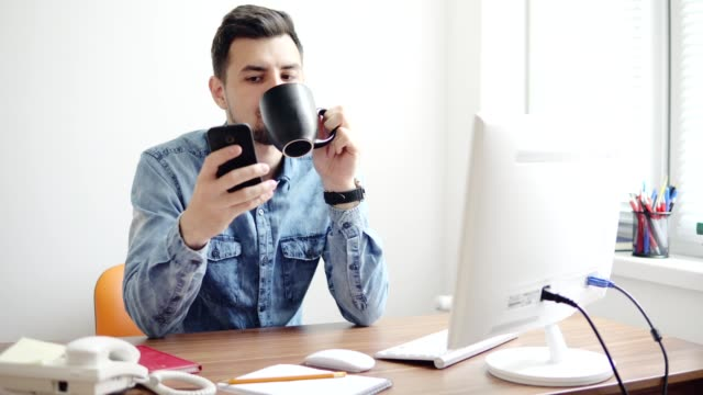 Young-office-worker-using-his-phone-at-the-office-sitting-at-the-table-with-computer-phone-and-drinking-coffee-or-tea-from-his-cup-Shot-in-4k